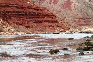 Wide river, mostly smooth, ruffled by wave, below steep cliffs of red and grey rock