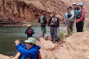 A group of rafters look out on the river, some taking photographs. Everyone wears hats and long sleeves and long pants.
