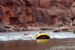 A bright yellow river raft dips down into a rapid from a smooth pool. Beyond another raft emerges from the rapids and the river ahead curves to the right as it meets a vertical rock wall of mottled red-and brown rock.