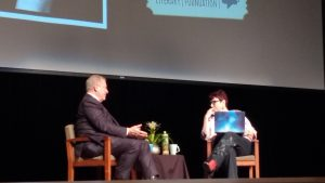 Al Gore sitting with Angie Coiro on a stage with a screen behind them and cups on a table in between their chairs. Angie is holding her laptop computer as she listens to Al answer a question.