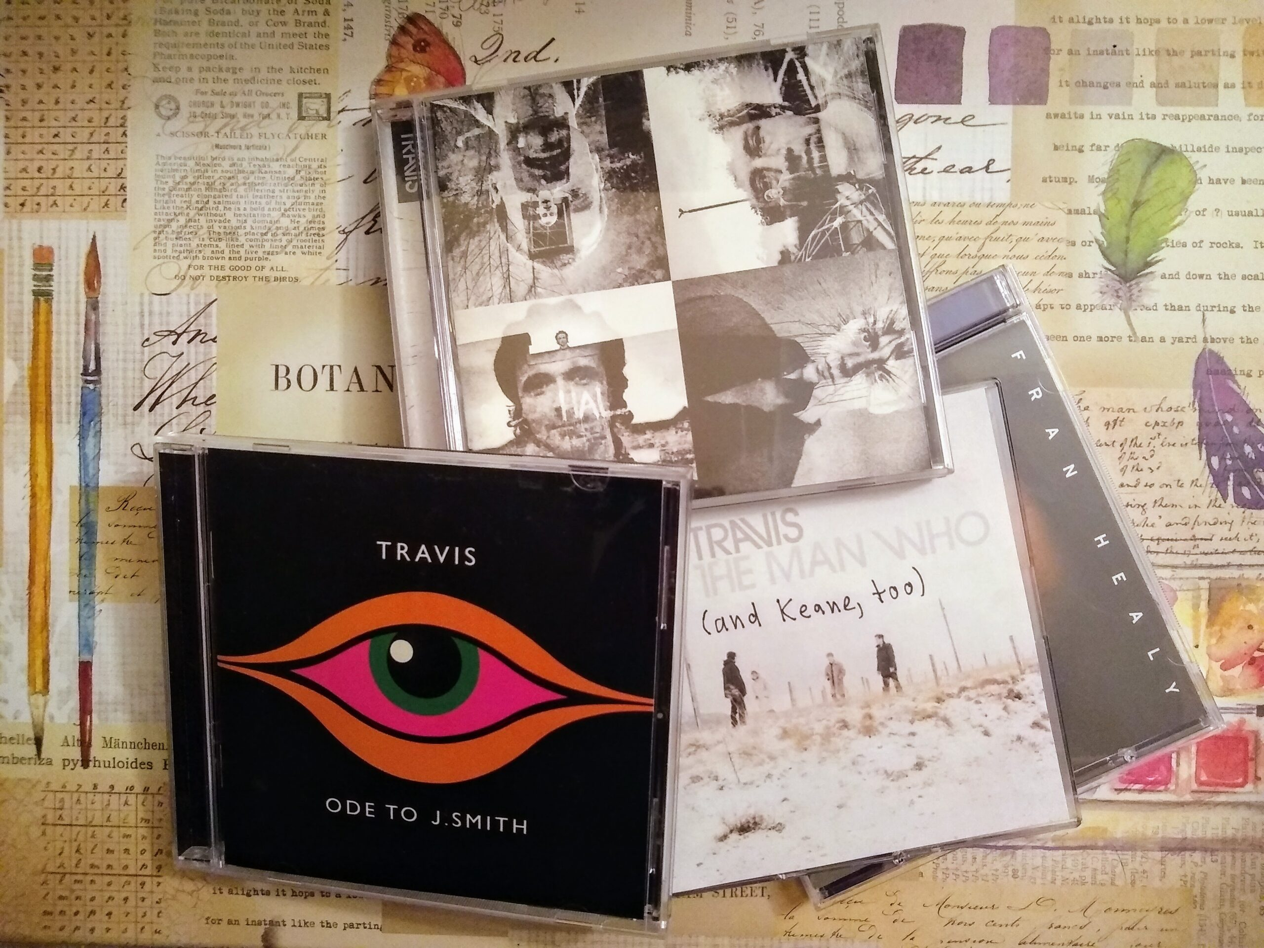 """Four music CD's scattered on top of a box with decorative printing. CD#1: a red eye between the words """"Travis"""" and """"Ode to J Smith"""". CD#2 four stylized black-and-white images of band members with text on edge """"Travis"""", a cover of a digital-download CD with misty figures in a landscape and text """"Travis The Man Who"""", CD#4 only text visible """"Fran Healy"""""""